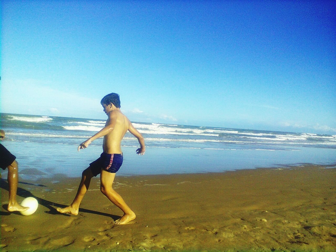 sea, shirtless, full length, beach, nature, water, real people, leisure activity, childhood, one person, sky, vacations, clear sky, scenics, blue, outdoors, beauty in nature, lifestyles, sand, boys, horizon over water, day, young adult, people