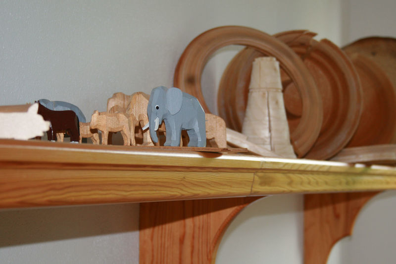 Wooden figurines over shelf on wall
