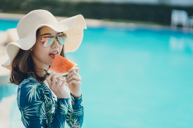 Portrait of young woman eating watermelon sitting by swimming pool
