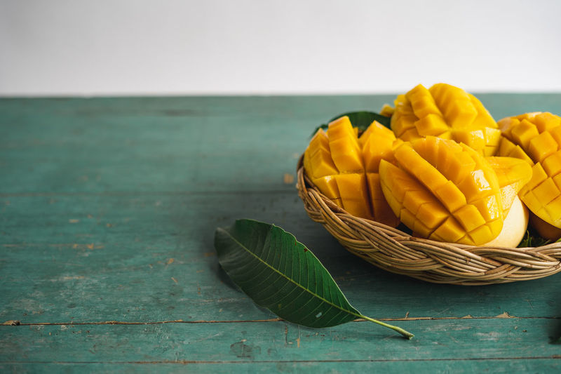 Mango in a basket on a green wood Food And Drink Food Freshness Table Healthy Eating Still Life Yellow Indoors  Wellbeing Vegetable No People Close-up Wood - Material Raw Food Green Color Plant Part Leaf Focus On Foreground Pasta Fruit