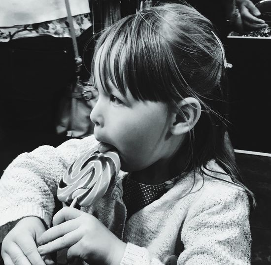 Close-up of cute girl licking candy in store