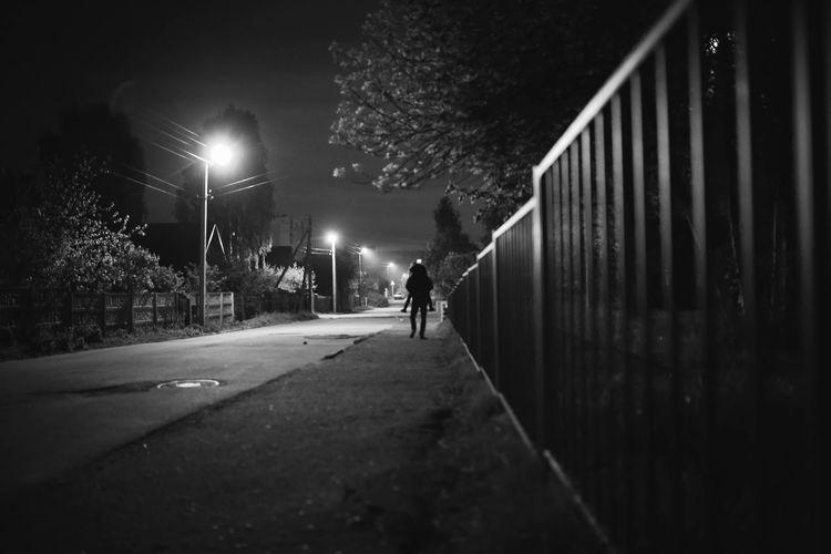 Man walking on road at night