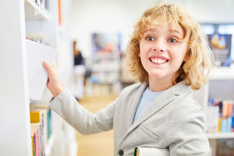 Smiling boy standing at library