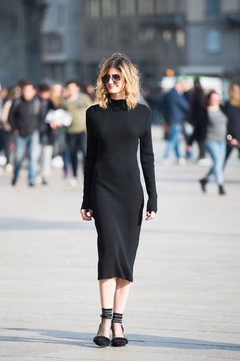 Beautiful young woman walking on street in city