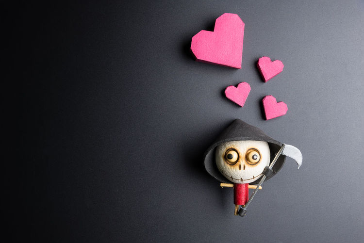 Directly above shot of heart shape with figurine over black background