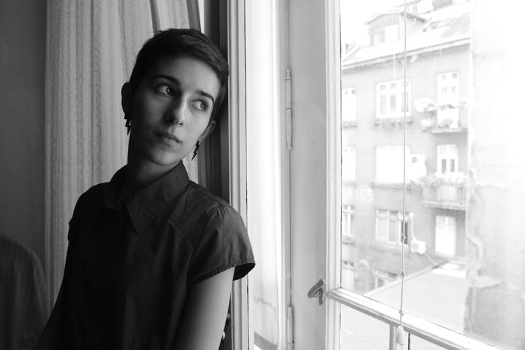 Portrait of young woman standing against window