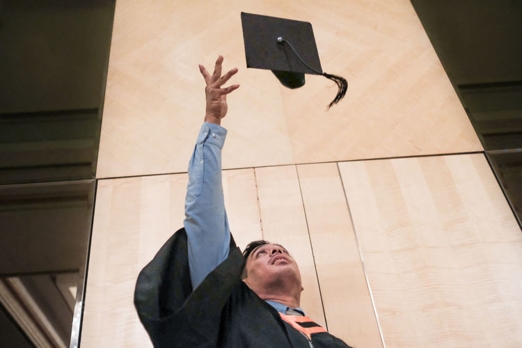 Low angle view of man throwing mortarboard while standing against wall