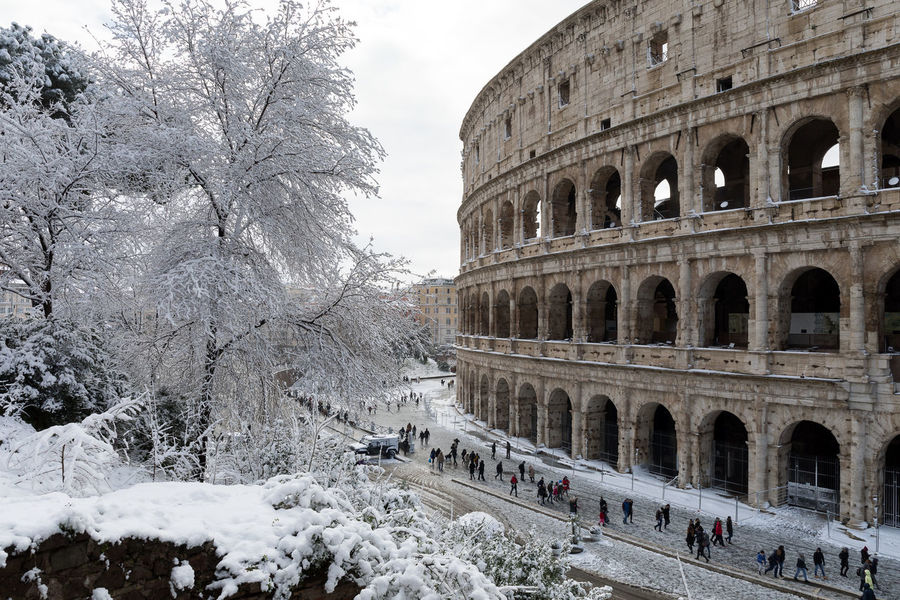 Rome, Italy - February 26, 2018: An exceptional weather event causes a cold and cold air across Europe, including Italy. Snow comes in the capital, covering streets and monuments of a white white coat. In the photo, the Colosseum covered by snow. Buran Ice Rome Snowy Days... Winter Arcade Architecture Building Exterior Built Structure Climate Change Colosseum Day History Monument Old Ruin Outdoors Polaroid Sky Snow Snowy Temperature Tourism Travel Destinations White Background Wind