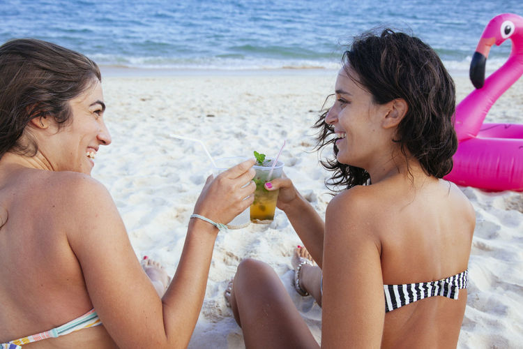 Happy friends sitting on shore at beach
