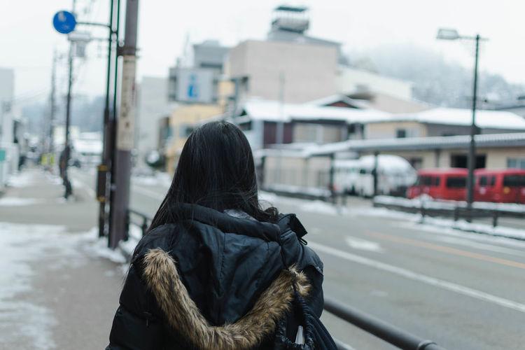 Rear view of woman on street in winter