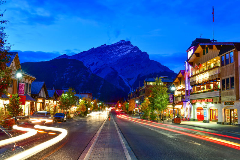 Street view of famous Banff Avenue at twilight time. Banff is a resort town and one of Canada's most popular tourist destinations. Illuminated Building Exterior Architecture Sky City Transportation Road Built Structure Mountain Street Light Trail Night Motion Dusk Long Exposure Blurred Motion Mode Of Transportation No People Sign Nature Mountain Range Outdoors Light Banff  Twilight Town Canada Avenue