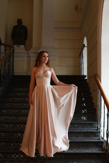 Smiling beautiful young woman wearing dress while standing on staircase