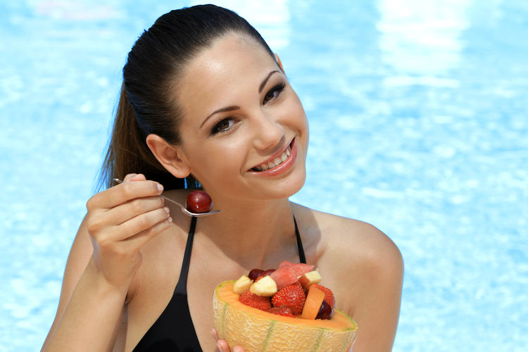 Portrait of beautiful smiling young woman having fruits against swimming pool