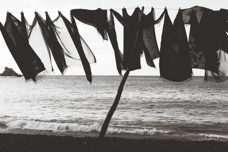 Clothes drying on clothesline at beach against sky