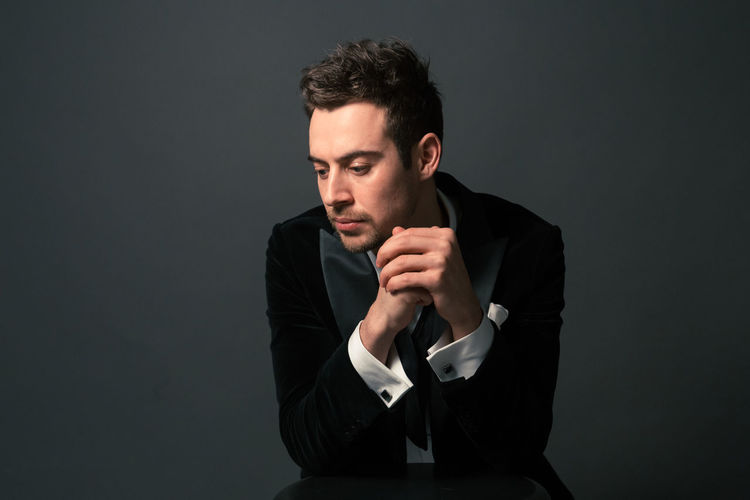 Thoughtful young man in suit sitting with hands clasped against gray background