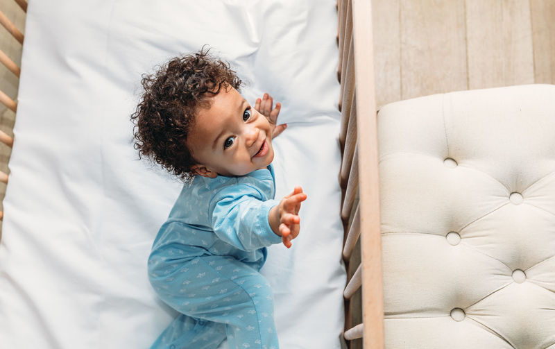 Childhood Child One Person Lifestyles Real People Indoors  Innocence Cute Toddler  Crib Indoors  Looking Innocence Kid Curly Hair Adorable African American Candid