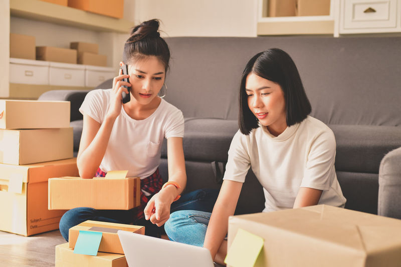 Adult Box Box - Container Cardboard Cardboard Box Casual Clothing Child Childhood Family Females Front View Indoors  Lifestyles Packing Sitting Sofa Togetherness Two People Women Young Adult Young Women