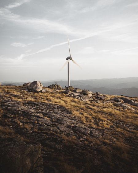 Wind turbine on mountain against sky