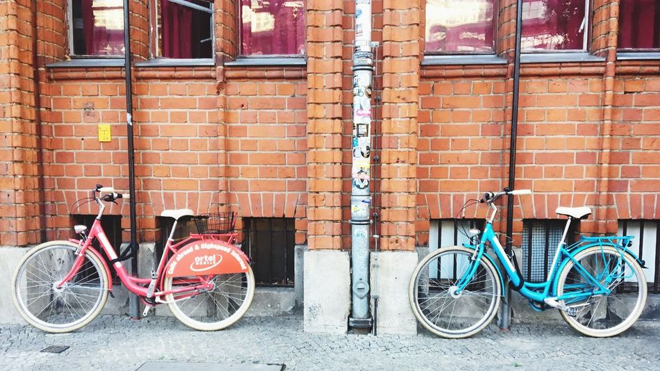 A couple Bike Bicycle Red Blue Wall Mode Of Transport Transportation Parking Brick Wall Parked City Life In Line Berlin Fahrrad Streetphotography Battle Of The Cities