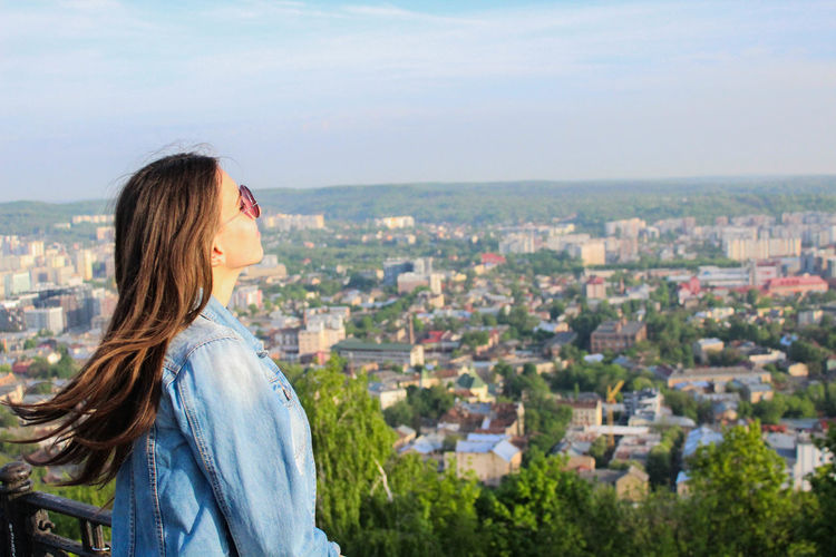 Side view of young woman looking at cityscape against sky