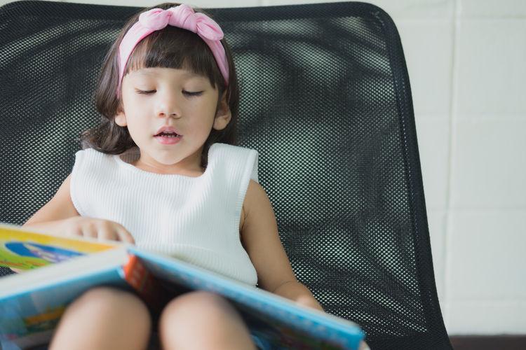 Full length of a girl sitting on book