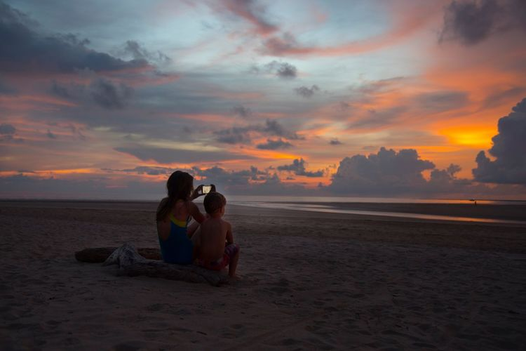 Couple sitting on beach against sky during sunset