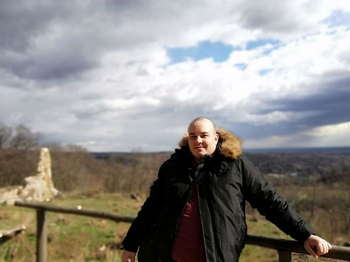 Portrait of woman standing in winter against sky