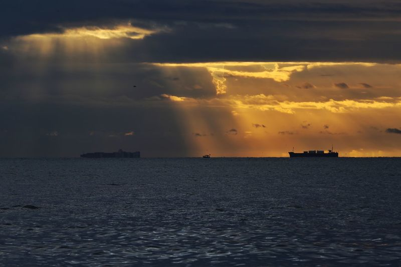 Cargo ship and sunset Sea Sky Water Cloud - Sky Scenics - Nature Sunset Beauty In Nature Horizon Over Water Horizon Waterfront Tranquil Scene Tranquility Nature No People Idyllic Orange Color Sunlight Dramatic Sky Outdoors