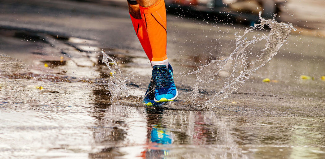 Low section of person running on puddle