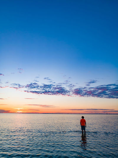 Rear view of boy standing in sea against sky during sunset