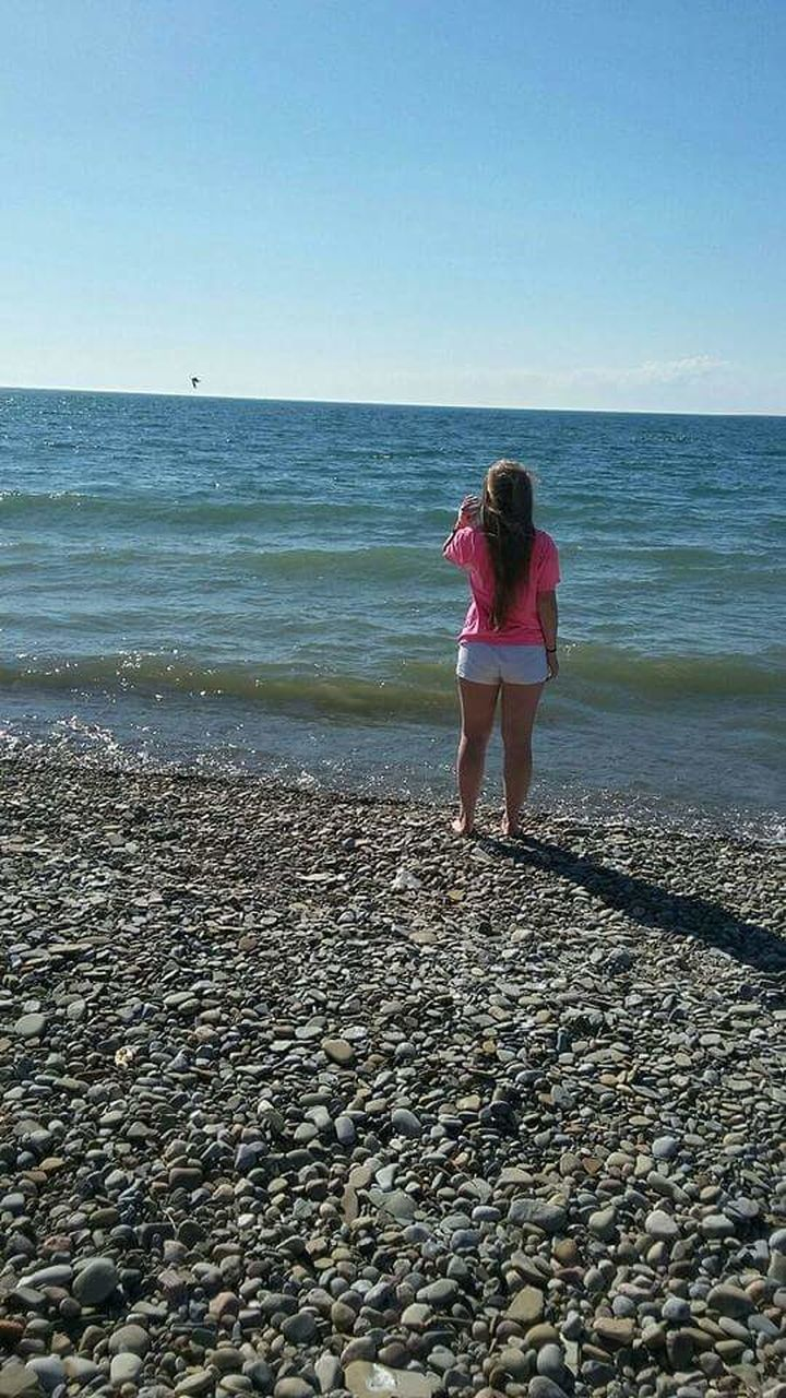 sea, horizon over water, beach, water, shore, standing, nature, rear view, leisure activity, pebble, scenics, full length, real people, beauty in nature, day, one person, sky, lifestyles, outdoors, vacations, pebble beach, young adult, young women, clear sky, adult, people