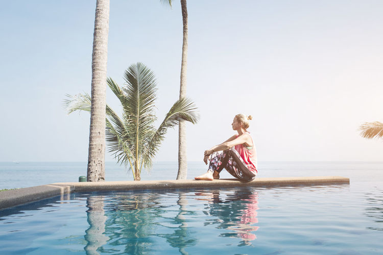 thoughtful woman sitting on the pool Adult Beach Beauty In Nature Bikini Clear Sky Day Full Length Happiness Horizon Over Water Leisure Activity Lifestyles Nature Outdoors Palm Tree Real People Scenics Sea Sitting Sky Swimming Pool Tree Vacations Water Young Adult Young Women
