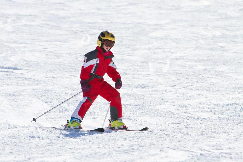 Teenage girl skiing on snow covered land