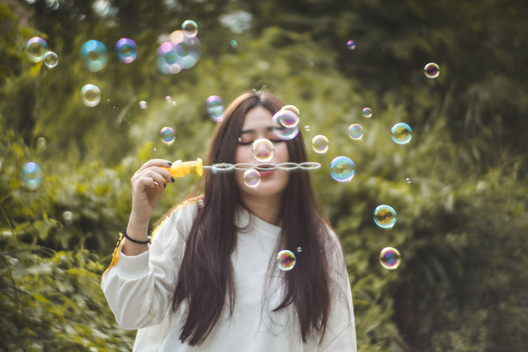Young woman blowing bubbles against trees