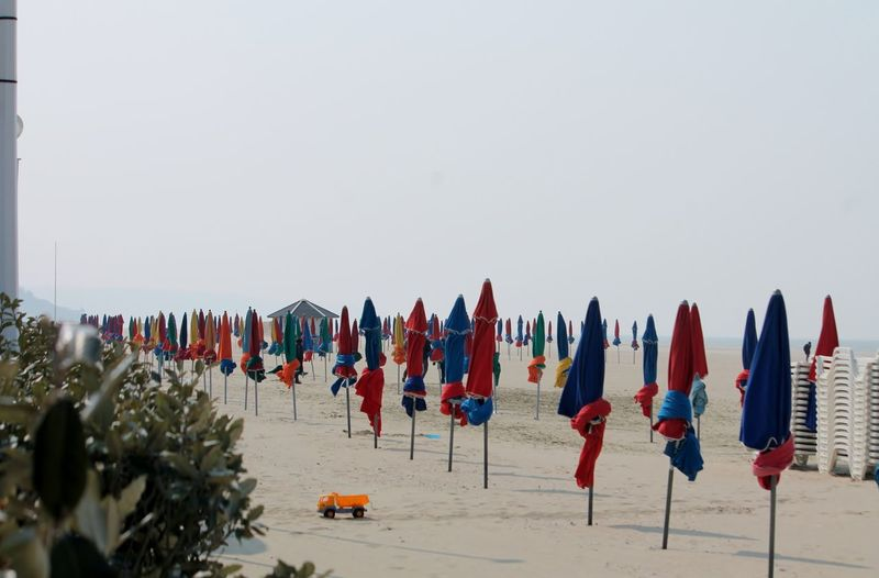 Closed canopies on beach against clear sky
