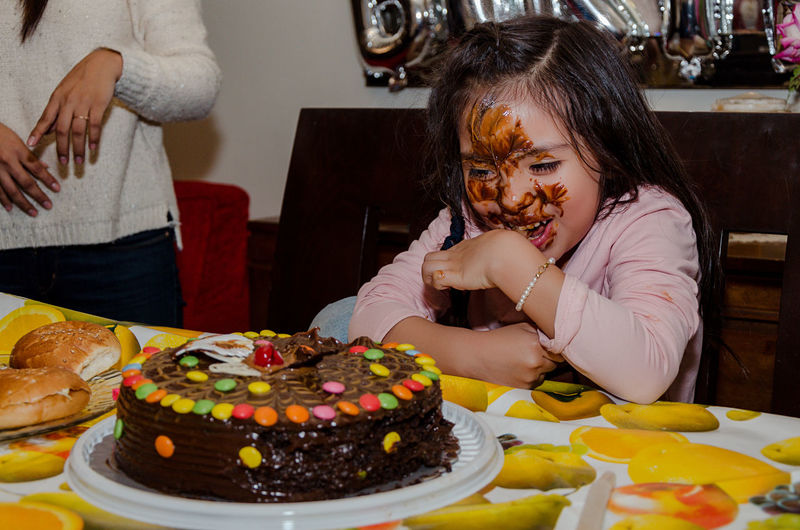 Smiling girl with cake on face during birthday party