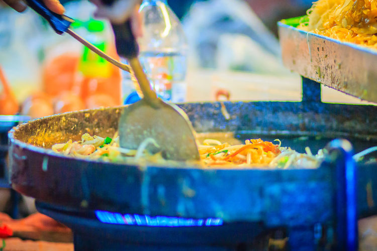 Close up hand of vendor during cooking for Padthai, the original Thai Fried Noodle, stir-fried noodle with shrimp and egg commonly served as a street food popular in Thailand Khao San Rd Khao San Road KhaoSan Khaosan Rd. Khaosandroad Pad Thai Shrimp Pad Thai With Shrimp Tourist Tourist Attraction  Tourists Business Close-up Container Food Food And Drink Freshness Healthy Eating Heat - Temperature Household Equipment Indoors  Khao San Khao San Knok Wua Khao San Rd. Khaosan Road Khaosanroad Kitchen Utensil Night Market Night Market In Thailand Night Market, No People Pad Thai Pad Thai Kung Padthai Padthai Food Padthai Grassnoodle Preparation  Preparing Food Ready-to-eat Retail  Selective Focus Spoon Still Life Stove Temptation Tourist Destination Wellbeing