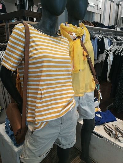 Boutique Casual Clothing Clothing Clothing Store Coathanger Consumerism Day Fashion For Sale Indoors  Lifestyles Mannequin Men Occupation People Real People Rear View Retail  Standing Store Textile Industry Two People Working Workshop Yellow