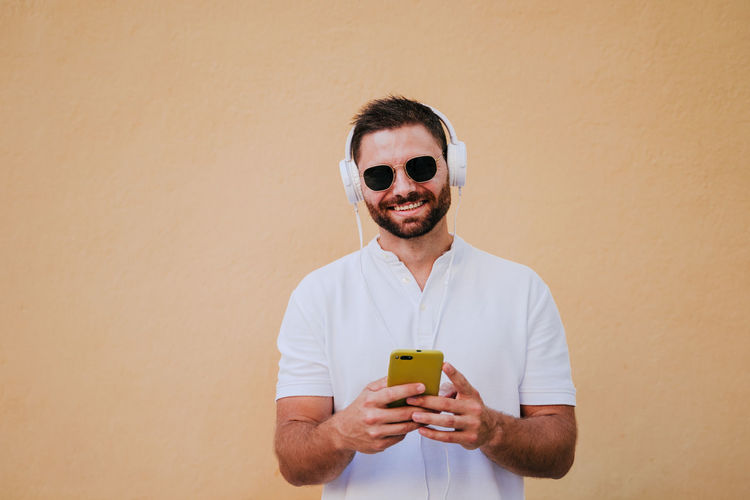 Portrait of smiling man holding camera while standing against wall
