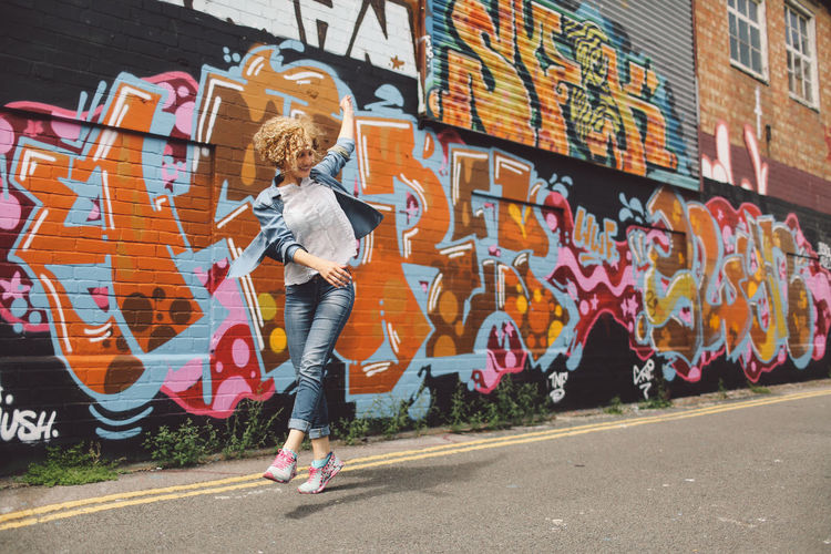 Art Blonde Brighton Casual Clothing City City Life Curly Hair Day Full Length Girl Graffiti Graffiti Graffiti Art Joyful Jumping Leisure Activity Lifestyles Multi Colored Outdoors Playful Spinning Street Art People And Places Art Is Everywhere Live For The Story Connected By Travel Fashion Stories #urbanana: The Urban Playground