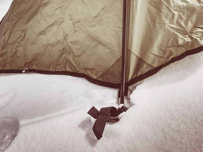Detail of tent anchorage on snow. a snow storm came within night and cover with fresh powder snow.