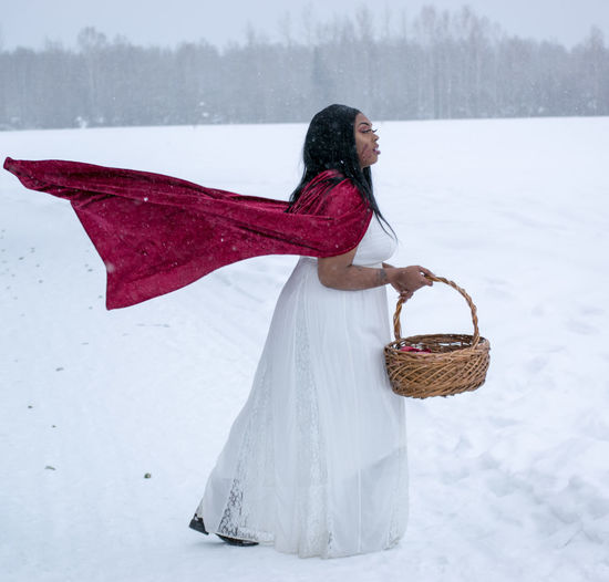 Side view of woman with red cape holding basket on landscape during winter