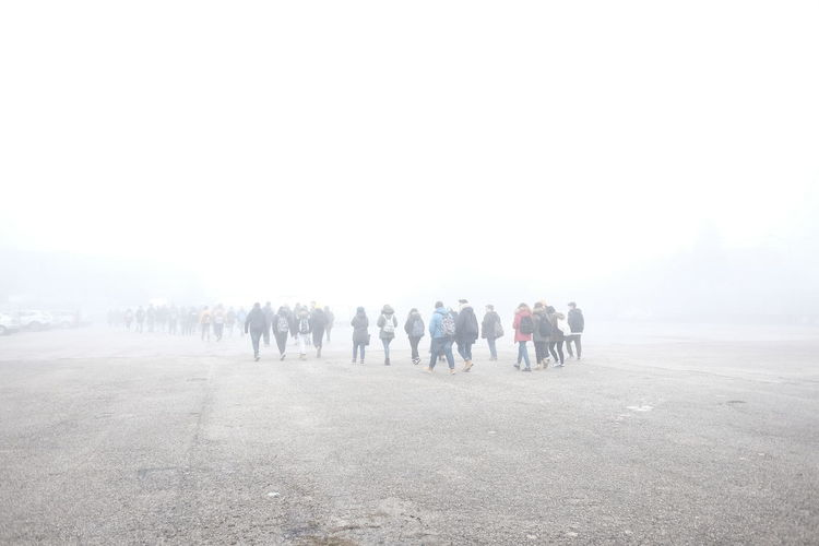 People walking on road against sky during foggy weather