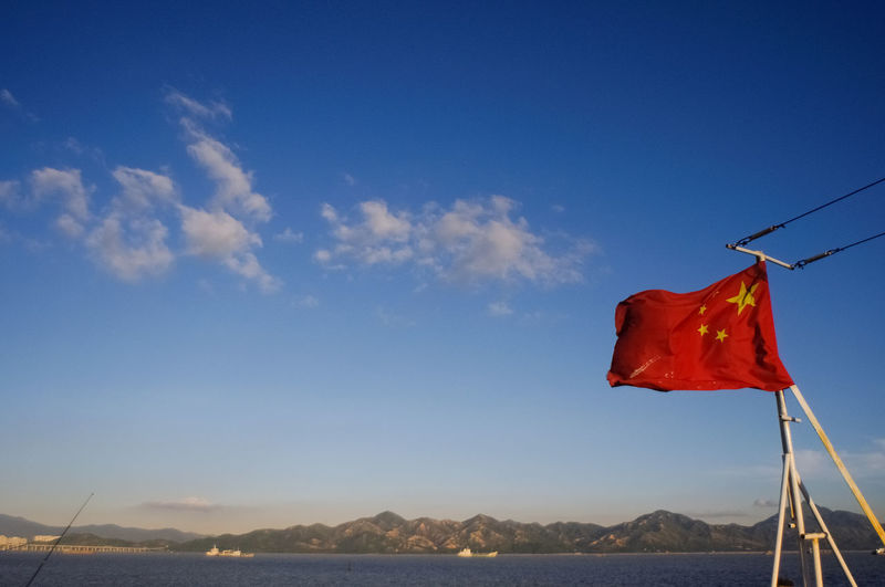 Low angle view of chinese flag against blue sky