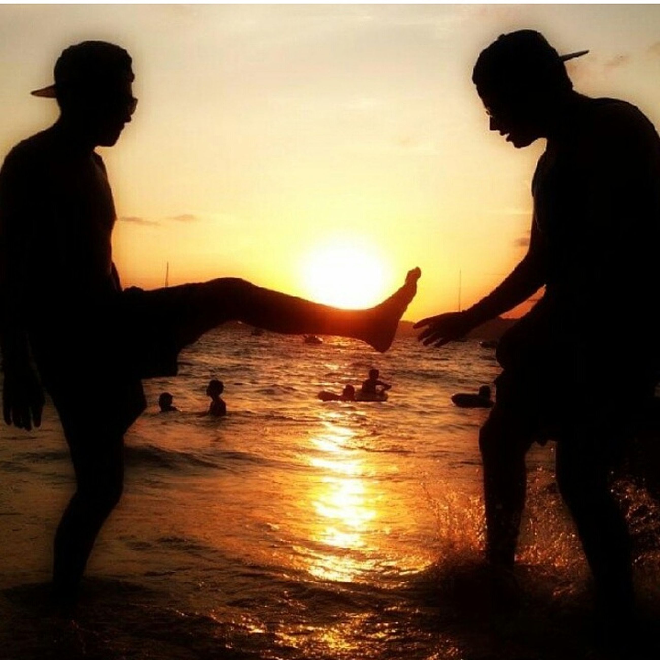 sunset, sun, silhouette, lifestyles, leisure activity, beach, sea, water, orange color, togetherness, person, sunlight, horizon over water, enjoyment, full length, bonding, standing