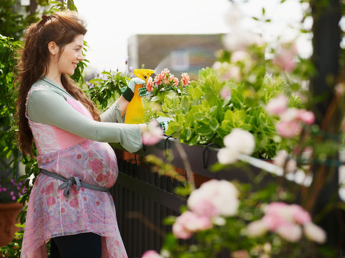 Side view of woman standing by flowering plants