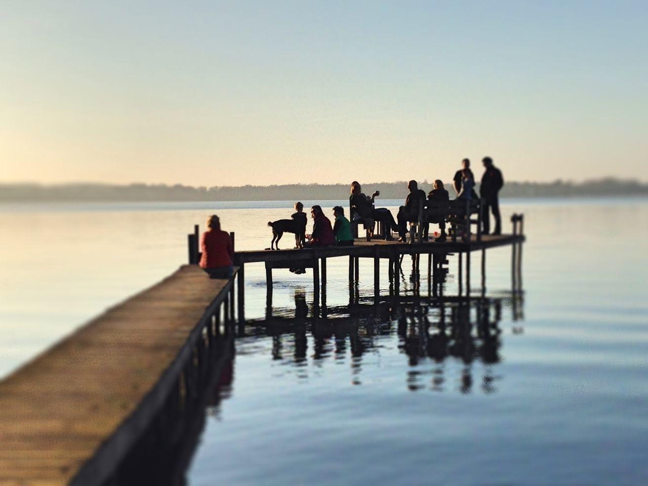 Tourists sitting on pier