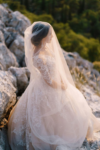 Side view of woman wearing gown standing on rock