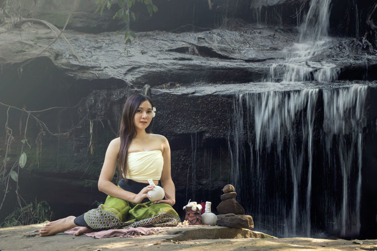 Portrait of smiling woman sitting on rock against waterfall