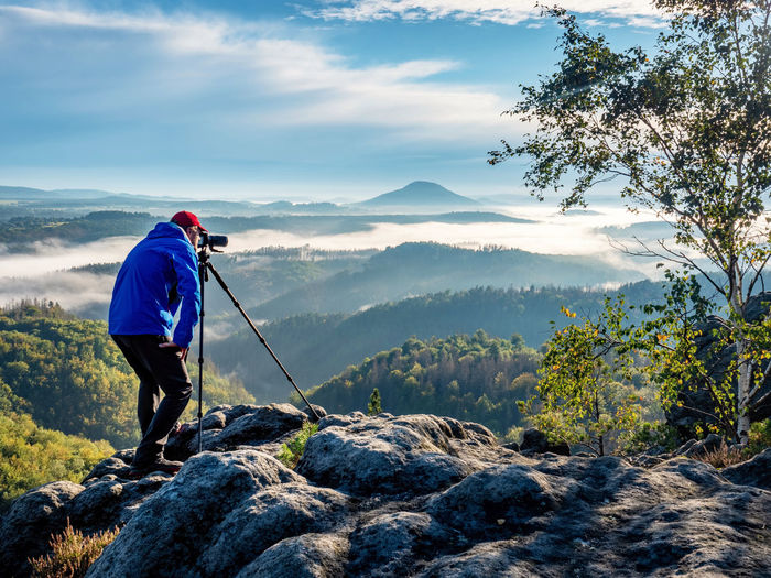 Outdoor travel photographer journalist holding a dslr camera in mountain background. man takes photo